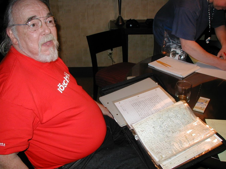 Gary Gygax vetää peliä GenConissa vuonna 2007. Gygaxin edessä olevassa kansiossa on ilmeisesti osia alkuperäisestä Castle Greyhawkista.